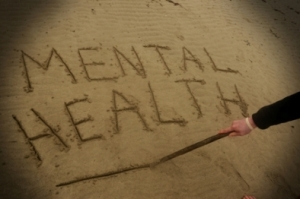 A young man suffering from depression writes the words mental health in the sand